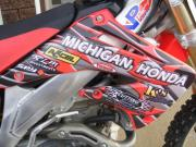 Another dirtbike wrapped with General Formulations MotoMark with various sponsor logos on it